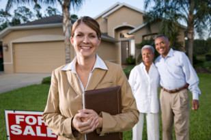 Realtor with African American couple outside house for sale